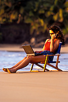 Woman uses a laptop and cell phone at the beach.