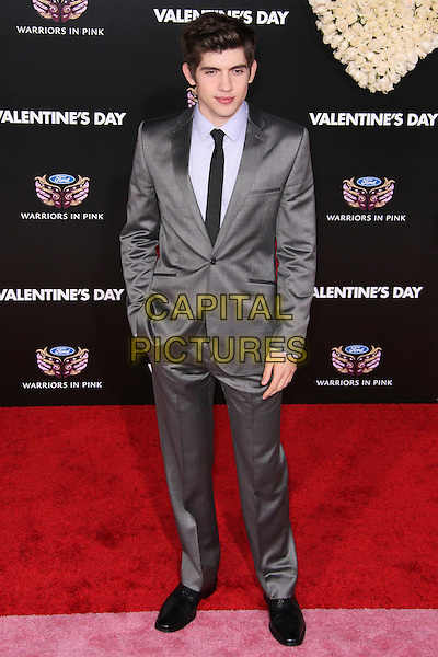 "CARTER JENKINS .Arrivals to the world premiere of ""Valentine's Day"" at Grauman's Chinese Theater in Hollywood, California, USA. .February 8th, 2010. .full length grey gray suit hand in pocket blue shirt tie black .CAP/CEL.©CelPh/Capital Pictures"