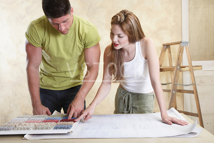 Couple looking at carpet samples and blueprint