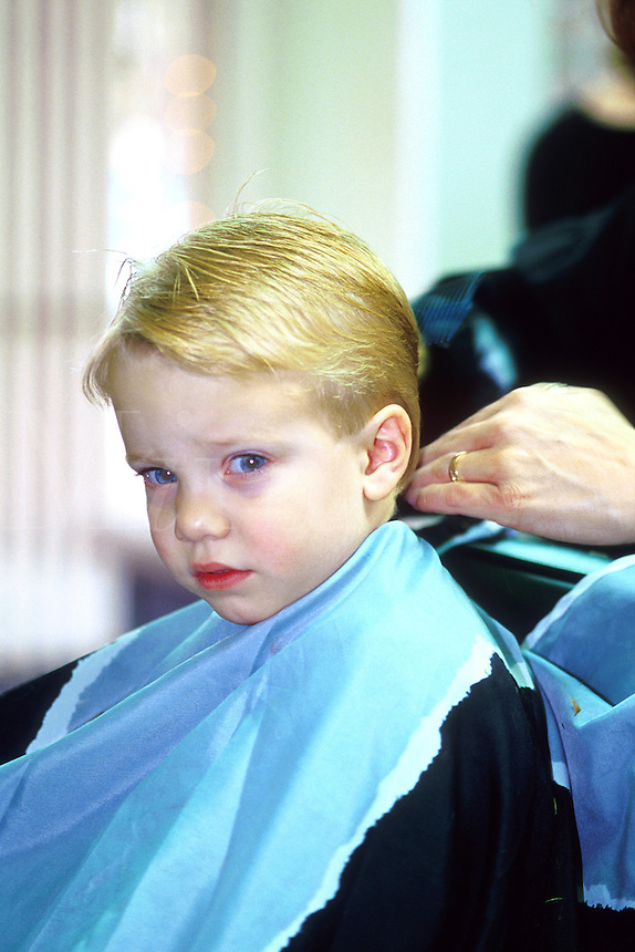 Child age 4 accepting haircut with less than modest enthusiasm.  Number 3 of a series of 3 images