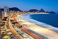 Dusk at Copacabana beach, Rio de Janeiro, Brazil. Traffic at Atlantica avenue, Sugar Loaf mountain in background. The promenade is a pavement landscape in large scale ( 4 kilometres long ) having a black and white Portuguese pavement design  by Roberto Burle Marx, a geometric wave.