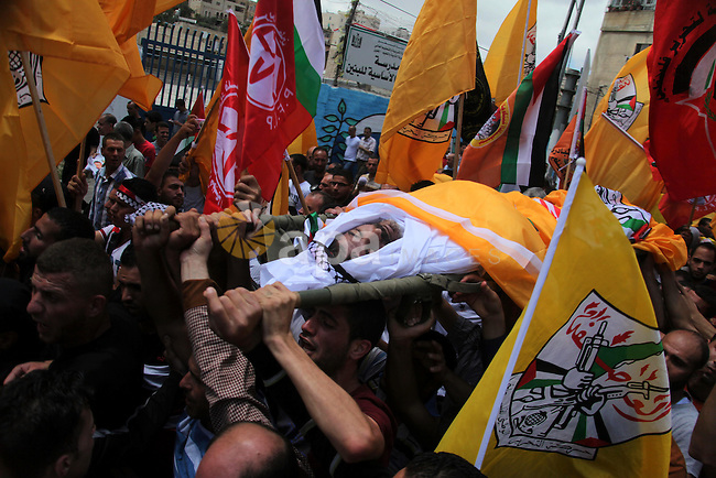 Mourners carry the body of Palestinian Nader Driss, whom medics said died of a gunshot wound by Israeli troops during clashes at a protest against the Israeli offensive in Gaza, during his funeral in the West Bank City of Hebron August 9, 2014. Violence picked up in the occupied West Bank, the Palestinian territory where President Mahmoud Abbas's Fatah movement holds sway, where Driss, a Palestinian man, 43, died of a gunshot wound to the chest from a confrontation with Israeli soldiers in the city of Hebron, medical officials said. Israeli troops shot and killed another Palestinian man, 20, on Friday at a protest near a Jewish settlement outside Ramallah, Israeli military officials said. Israel launched more than 20 aerial attacks in Gaza on Saturday, killing five Palestinians, and militants fired rockets at Israel as the conflict entered a second month, defying international efforts to negotiate an agreement for an extended ceasefire. Photo by Mamoun Wazwaz
