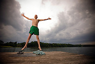 An elderly man jumps up in the air on a pier off a lake.