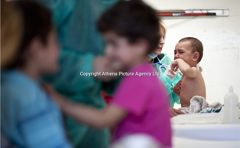 Pictured: Young children are assessed by doctors Thursday 03 March 2016<br /> Re: Migrants have been gathering at the port of Piraeus, near Athens, Greece