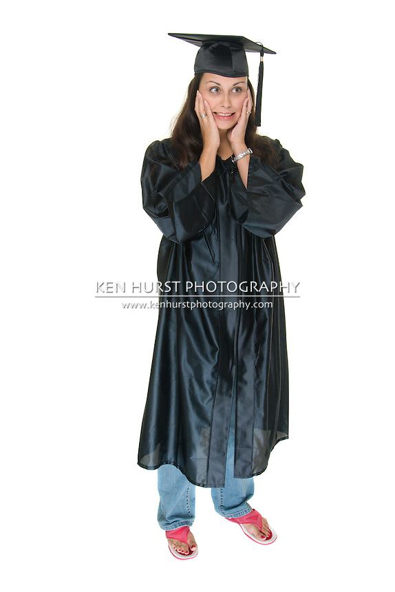 Beautiful young woman standing in graduation robes with bright pink flip flop shoes holding her hands to her cheeks in excitement about graduation.