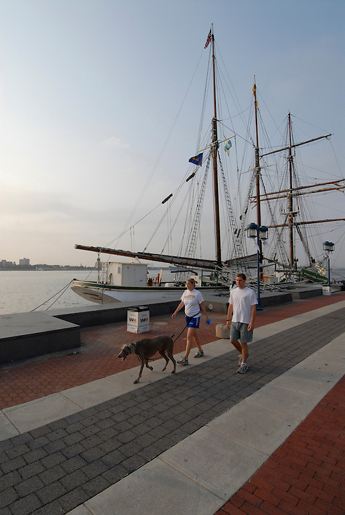 Penn's Landing, couple walking dog, mod rel..Philadelphia, Pennsylvania, PA USA.  Photo copyright Lee Foster, 510-549-2202, lee@fostertravel.com, www.fostertravel.com. Photo 239-30400