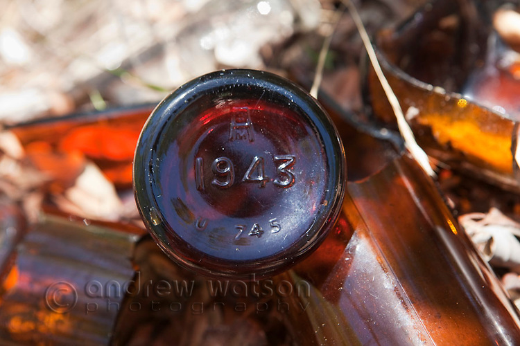 Beer bottles stamped with the year 1943 - remnants of World War II soldiers on Horn Island.  The island was a strategic outpost during WWII and was bombed numerous times by the Japanese.  Horn Island, Torres Strait Islands, Queensland, Australia