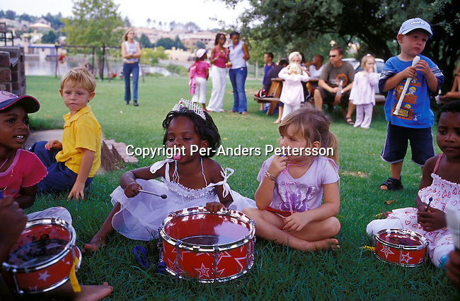 JOHANNESBURG, SOUTH AFRICA - FEBRUARY 29:Lebone Dube (center), age 4, playing intruments with her friends at her birthday party on February 29, 2004 in Cedar Lake, a up-market gated community in Johannesburg, South Africa Her father, Oscar Dube, works as a Key Account manager for the Swedish mobile phone equipment maker Ericsson and his wife, Mpho Dube, is fund manager at Old Mutual, an insurance company in SA. They belong to the new black elite in SA. Lebone attends an exclusive pre-school with mostly white children and she invited them for her birthday party. Well educated and connected, they have risen from the poverty in the townships to a very different lifestyle, since the fall of Apartheid and the start of democracy in the country in 1994. .Photo: Per-Anders Pettersson/iAfrika Photos....