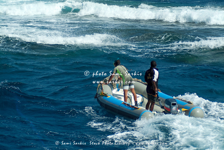 Two men steering an inflatable boat through the surf, Red Sea, Egypt.