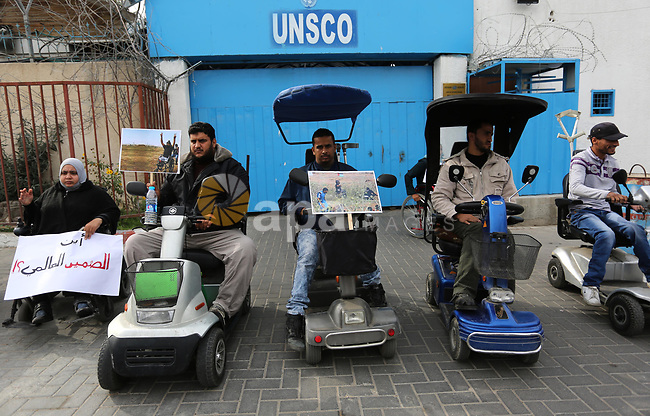 """Disabled Palestinians take part in a protest against the killing of Ibraheem Abu Thuraya in front of the headquarter United Nation """"UNESCO"""", in Gaza City, on December 21, 2017. Abu Thuraya, who was shot dead by Israeli security forces during clashes near the border with Israel in the east of Gaza City against U.S. President Donald Trump's decision to recognize Jerusalem as the capital of Israel. Photo by Ashraf Amra"""