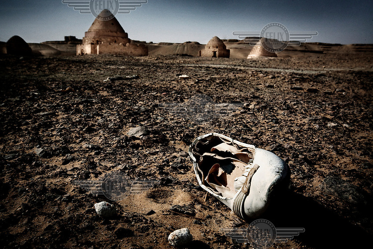 An abandoned slipper lies in the rocky desert that stretches to the tombs of Sheikh Nasr...