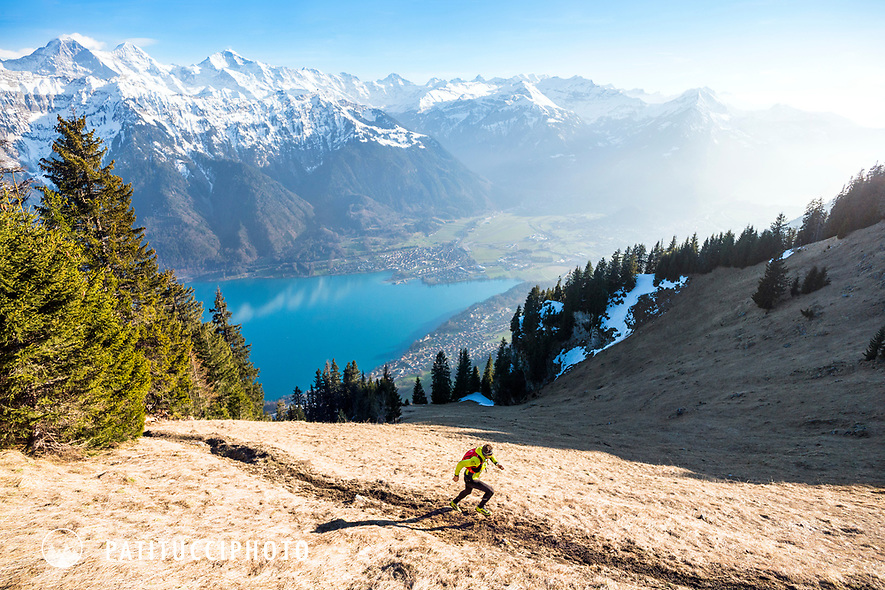 Ueli Steck trail running on a sunny spring day high above Lake Brienz (Brienzersee) and Interlaken, with views out to the famous mountains of the Eiger, Mönch and Jungfrau, Switzerland