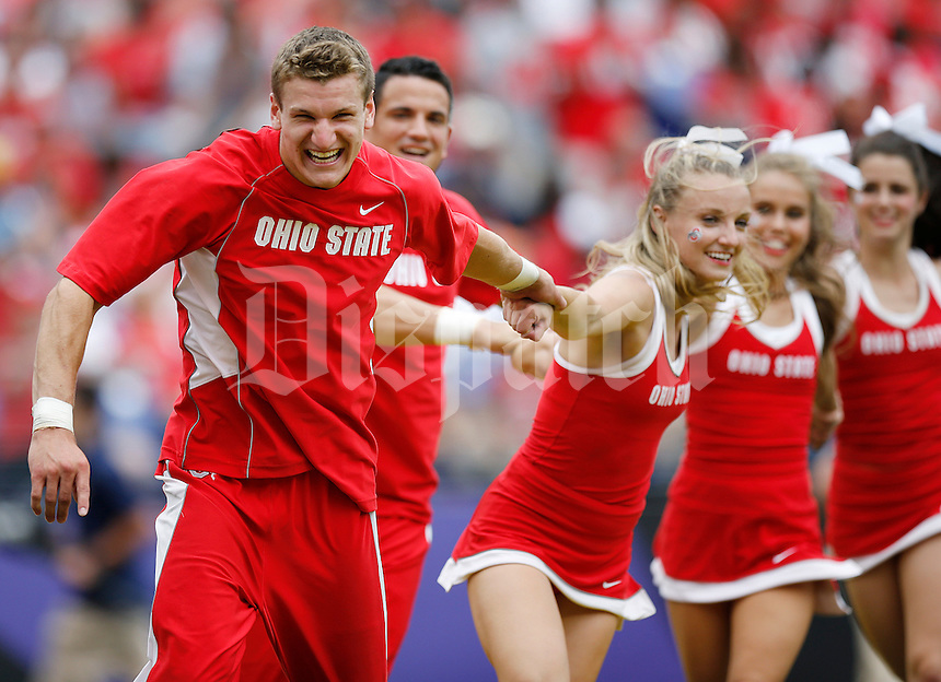 Ohio State cheerleaders celebrate a touchdown during the college football game between the Ohio State Buckeyes and the Navy Midshipmen at M&T Bank Stadium in Baltimore, Saturday afternoon, August 30, 2014. The Ohio State Buckeyes defeated the Navy Midshipmen 34 - 17. (The Columbus Dispatch / Eamon Queeney)
