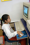 Oakland CA 2nd grade student absorbed in educational computer program in class