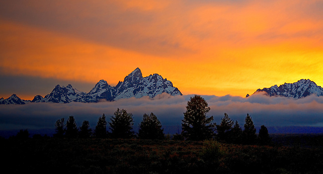 THE SUN SETS BEHIND THE GRAND TETONS AND A LAYER OF FOG AFTER A THUNDERSTORM IN GRAND TETON NATIONAL PARK,WYOMING