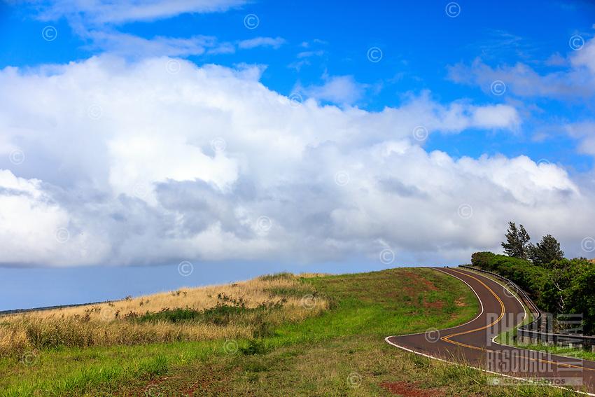 Waimea Canyon Drive curves over a green hillside in Waimea, Kaua'i.