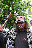 A man participating in the Zombie Walk in Prague 2014, wearing a mask with yellow teeth, and another mask in his forehead, holding an axe in his bloody right hand. Wearing dark blue t-shirt and check pattern shirt in blue and white, in the background branches from a tree and part of a building.