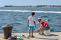 A father and son, fishing, at the head of the peninsula, Zadar, Croatia.