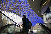 Man with luggage on an escalator beneath the roof of the newly refurbished Kings Cross station, London.