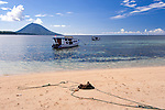 Dive and excursion boats pick up and drop off passengers on the beach at Siladen Resort and Spa, using mooring lines already in place on the beach for that purpose.  At night boats are moored off the beach, between Siladen Island and the neighboring islands of Bunaken and volcanic Manado tua, in the distance.  (Siladen Resort and Spa, Siladen Island, off North Sulawesi, Indonesia.)