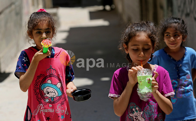 Palestinian children blow bubbles at street during a heatwave in Beit Lahia in the northern of Gaza Strip, on July 4, 2017. Photo by Ashraf Amra