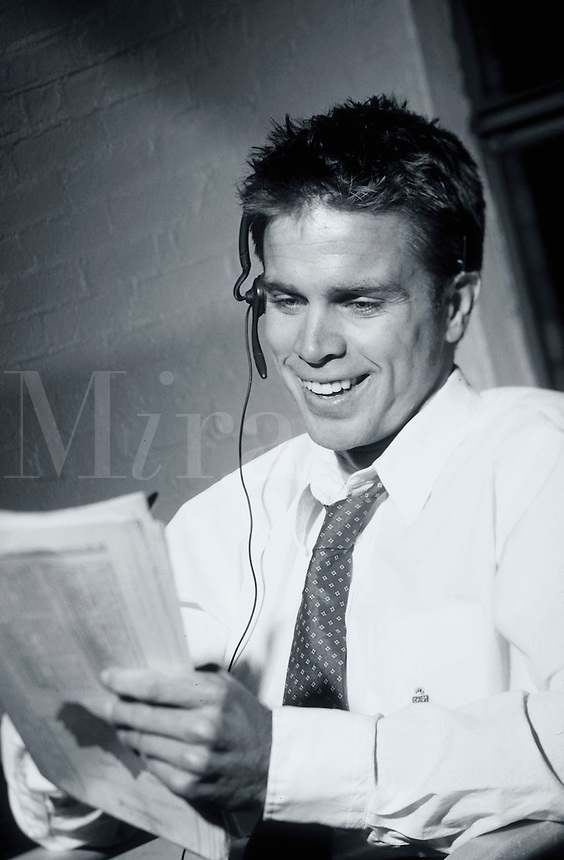A smiling young executive man with a phone headset looking at a newspaper.