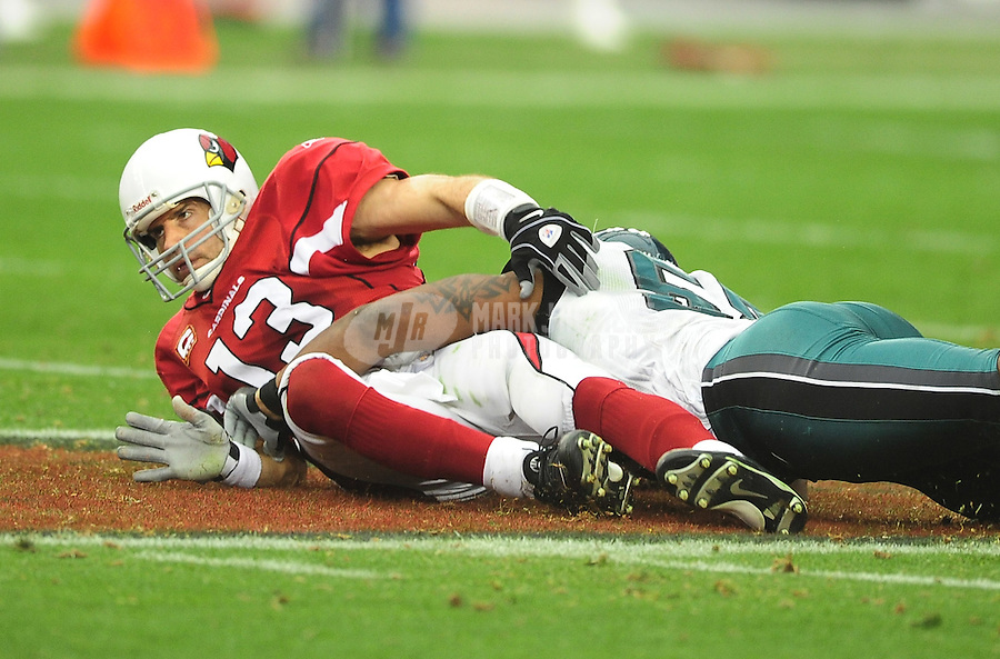 Jan. 18, 2009; Glendale, AZ, USA; Arizona Cardinals quarterback (13) Kurt Warner lays on the ground after being tackled against the Philadelphia Eagles during the NFC Championship game at University of Phoenix Stadium. Arizona defeated the Eagles 32-25 to advance to the Super Bowl. Mandatory Credit: Mark J. Rebilas-