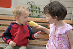 Sausalito CA Girl four-years-old letting her brother, two, sample her popsicle  MR
