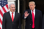 US President Donald J. Trump (R) waves beside Prime Minister of Israel Benjamin Netanyahu (L) while greeting him at the South Portico of the White House in Washington, DC, USA, 25 March 2019. Trump later signed an order recognizing Golan Heights as Israeli territory.<br /> Credit: Michael Reynolds / Pool via CNP