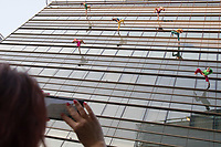 Viewer takes pictures with his mobile phone as members of the Bandaloop company from USA perform on the glass wall of an office building during the the CAFe Contemporary Art Festival in downtown Budapest, Hungary on Oct. 20, 2017. ATTILA VOLGYI