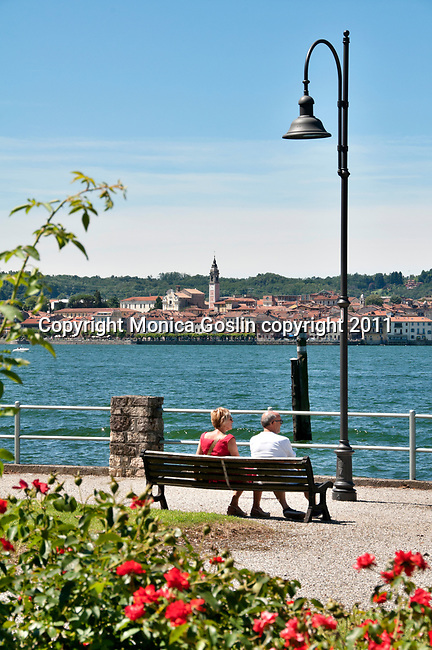 A couple sits on a bench in the town of Angera, looking across Lake Maggiore, Italy at the town of Arona