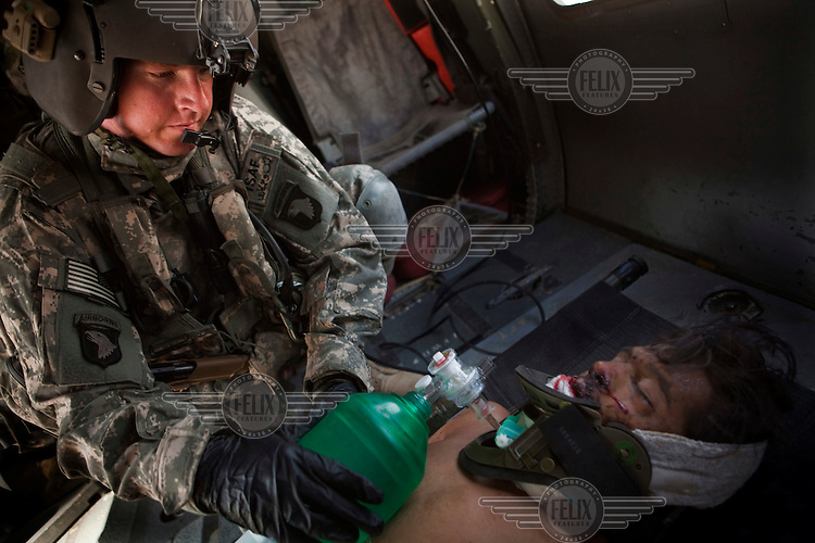An Afghan National Army (ANA) soldier is treated by US Army medics on board a medevac helicopter from Charlie Company, Sixth Battalion, 101st Aviation Regiment after his vehicle hit an IED (improvised explosive device) near Kandahar.
