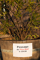 paper sign posted on a plant pot saying that Father Christmas Santa Claus with come by the restaurant at 15.30 3.30 PM. Domaine Gerard Bertrand, Chateau l'Hospitalet. La Clape. Languedoc. France. Europe.
