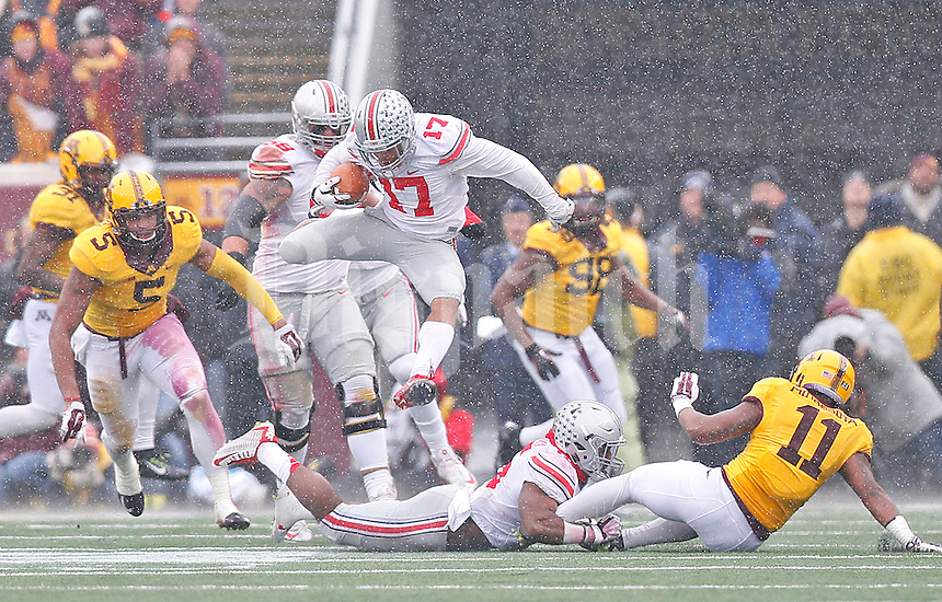 Ohio State Buckeyes running back Jalin Marshall (17) jumps over a blocker to get more yards in the second half at TCF Bank Stadium on November 15, 2014. (Chris Russell/Dispatch Photo)