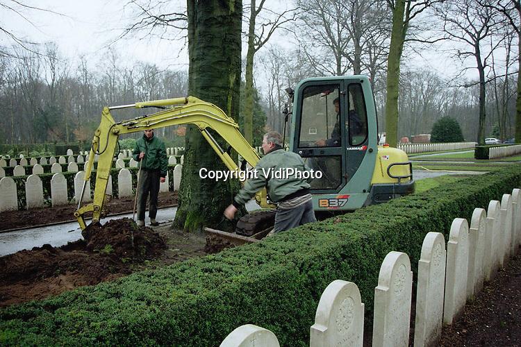 Foto: VidiPhoto..RHENEN - Met man en macht wordt er gewerkt om het gras op de Nederlandse oorlogsgraven op de Grebbeberg in Rhenen weer in orde te krijgen. Het heeft er nog nooit zo slecht uitgezien, vertelt medewerker T. van Rijn van de Oorlogsgravenstichting. Oorzaak is het aanhoudende natte weer. Daardoor krijgt het gras geen kans om zich te herstellen en grijpt het mos zijn kans. Op dit moment wordt het gras voor de zerken en het gazon .tegenover de graven machinaal verwijderd en opnieuw ingezaaid. Voor dodenherdenking 4 mei moet alles weer piekfijn in orde zijn. .