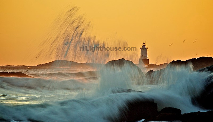 Birds fly past crashing waves at Sakonnet Point Lighthouse.