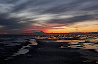 The sun paints a vibrant scene behind Mount Iliamna and the Aleutian Range as it sets with Cook Inlet's glacial mud exposed at low tide.