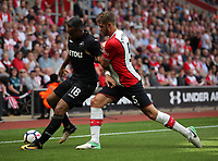 (L-R) Jordan Ayew of Swansea City challenged by Jack Stephens of Southampton during the Premier League match between Southampton and Swansea City at the St Mary's Stadium, Southampton, England, UK. Saturday 12 August 2017