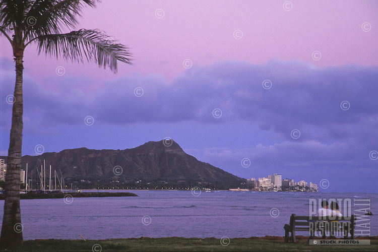 A couple enjoys the view of Diamond Head at dusk in Waikiki, Oahu