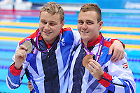 PICTURE BY ALEX BROADWAY /SWPIX.COM - 2012 London Paralympic Games - Day Two - Swimming - Aquatic Centre, Olympic Park, London, England - 31/08/12 - Sam & Oliver Hynd pose with their medals after winning Silver & Bronze in the Men's 400m Freestyle S8.
