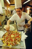 A Chef preparing a paella in Gibralfaro restaurant car of Al Andalus Expreso.