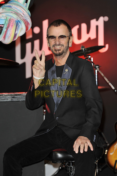 Ringo Starr.Unveiling of the 'Knotted Gun' statue for the Non Violence Foundation, Gibson Guitar Studio, London, England. .8th December 2011.half length black suit sunglasses shades beard facial hair hand v peace sign sitting .CAP/MAR.© Martin Harris/Capital Pictures.