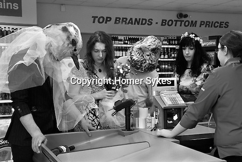 Made In Spring. Roath Cardiff Wales. The May Queen Beth Greenhalgh and her attendants purchasing some refreshments in Home Bargains. May 2014
