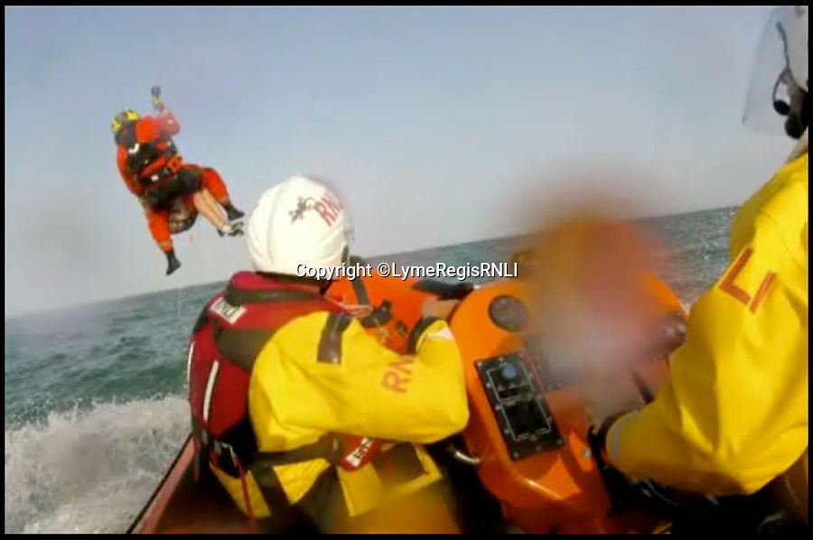 BNPS.co.uk (01202 558833)<br /> Pic :  LymeRegisRNLI/BNPS<br /> <br /> The boys are winched to safety by the helicopter.<br /> <br /> This is the dramatic moment two teenage tombstoners were saved from drowning after they were swept 250 yards out to sea.<br /> <br /> Archie Woollacott, 14, got dragged away by a strong current after plunging off a harbour wall at Axmouth, Devon. His friend Bozhidrar Bobev jumped in to rescue him but was also taken out to sea.<br /> <br /> The stricken pair spent an hour treading water before they were spotted by the Lyme Regis lifeboat crew in the nick of time.<br /> <br /> The next day Archie visited to RNLI station to thank the crew by baking them a lemon drizzle cake.