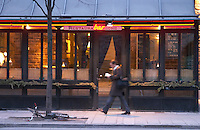 The trendy restaurant Riche with its wine bar. A man walking past reading a book and a bicycle parked by a tree but fallen. Stockholm, Sweden, Sverige, Europe