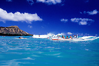 EDITORIAL ONLY. Tourists in outrigger canoe near Waikiki and Diamond Head