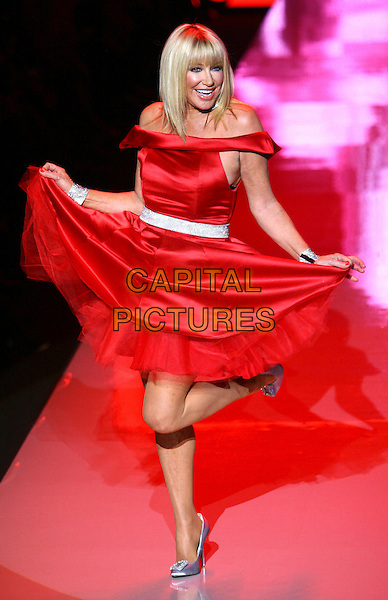 SUZANNE SOMERS .The Heart Truth Fall 2011 fashion show during Mercedes-Benz Fashion Week at The Theatre at Lincoln Center on New York City, New York, NY, USA,.9th February 2011..catwalk runway model modeling full length red dress tulle hands holding skirt  off the shoulders silk satin silver cuffs shoes belt posing funny standing on one foot leg .CAP/ADM/PZ.©Paul Zimmerman/AdMedia/Capital Pictures.