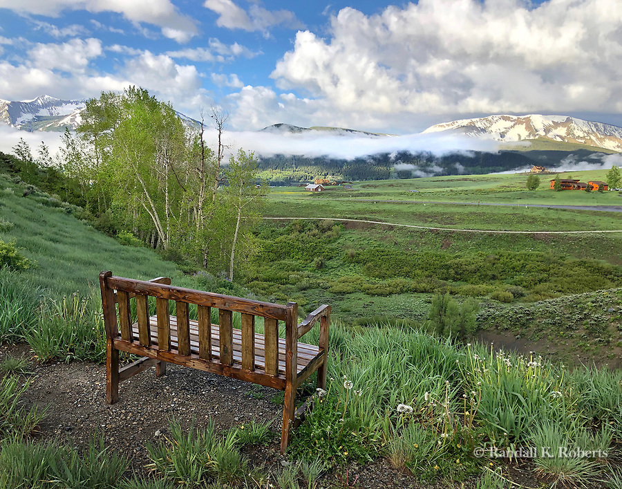 A bench's view of low clouds over Crested Butte, Colorado