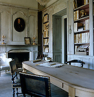 The walls of the library and office are covered with distressed panelling and the room is dominated by a scrubbed wooden table
