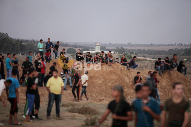 Palestinian protesters gather during clashes with Israeli troops near a border fence between Israel and the Gaza Strip on October 14, 2015 east of Bureij in central Gaza. The outbreak of violence between Palestinians and Israeli forces in recent weeks has worsened in October, raising fears of a third intifada, or uprising. Photo by Ashraf Amra